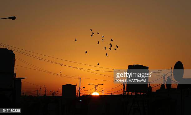 Electricity cables and poles are seen as the sun sets at the Zaatari refugee camp located close to the northern Jordanian city of Mafraq near the...