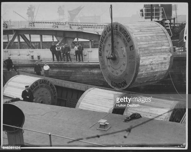Electricity cables from the Enfield works in London are lifted from a boat.