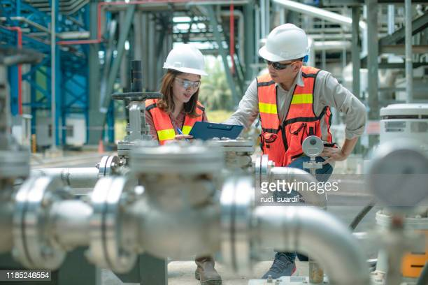 electricity engineer and his supervisor at industrial facility - power station stock pictures, royalty-free photos & images