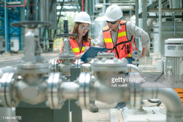 electricity engineer and his supervisor at industrial facility - industry stock pictures, royalty-free photos & images