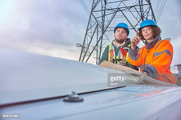 electricity engineers beneath a pylon