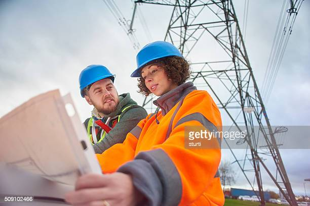 electricity engineers beneath a pylon