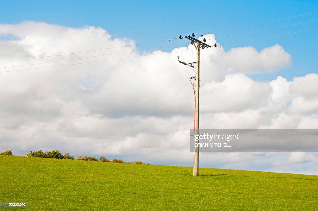 Electricity high voltage cable pole in a rural setting : Stock Photo