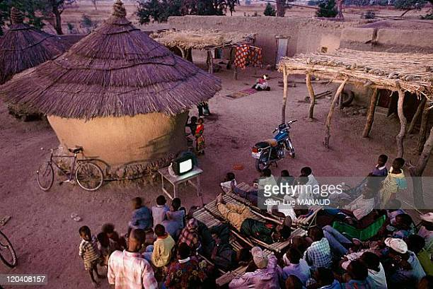 Electricity in Mali Men and children watching a football match on a television which is supplied by solar energy