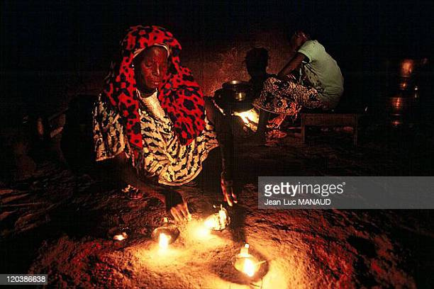 Electricity in Mali Preparing the evening meal using light from a shea butter lamp