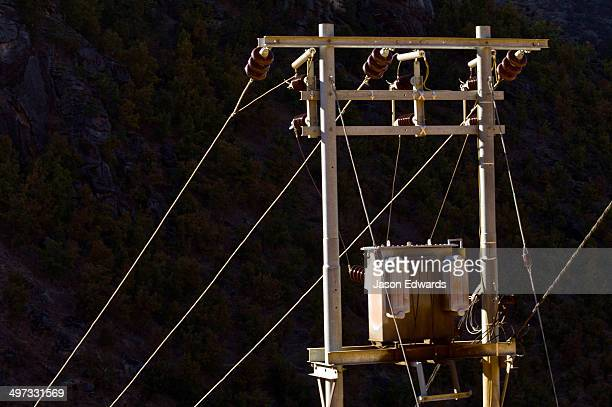 Electricity pole, cables and transformer catch the sunset as a mountain valley falls into shadow.