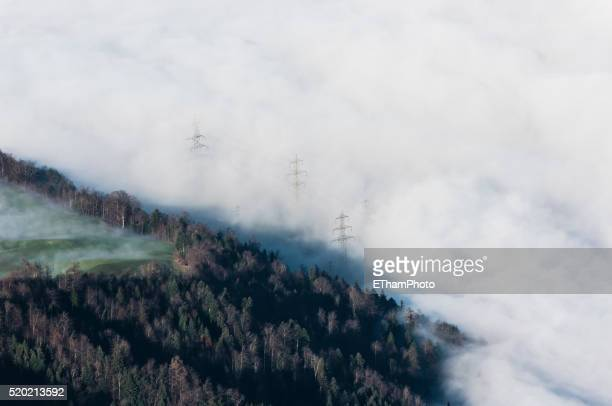 Electricity pole disappearing in sea of clouds