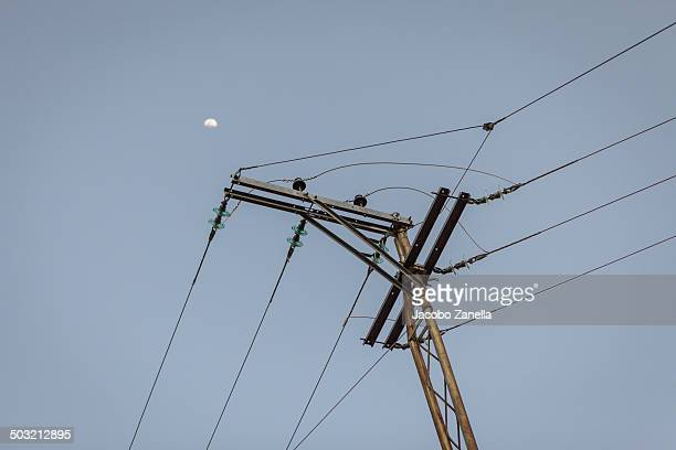 Electricity Pole With The Moon In The Distance Stock Photo