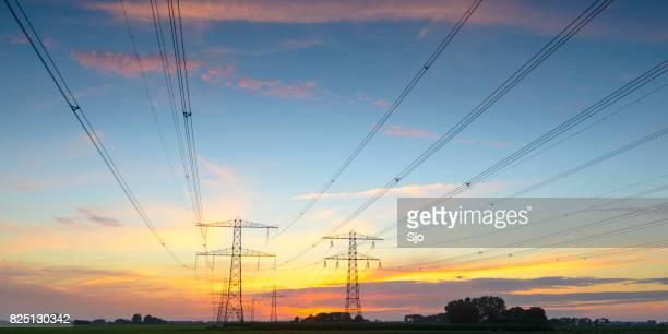 Poteaux électriques dans un paysage vide pendant le coucher du soleil