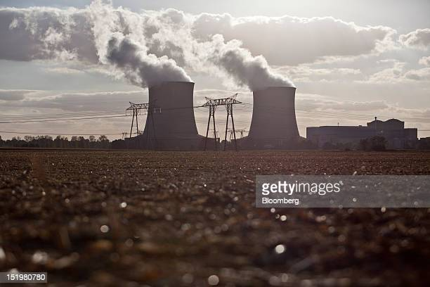 Electricity power cables run past cooling towers at the SaintLaurentdesEaux nuclear power plant operated by Electricite de France SA in...