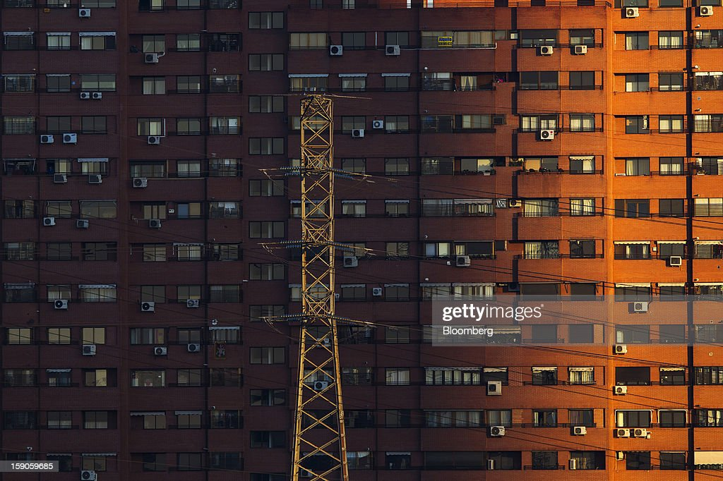 Electricity power lines hang from a pylon near residential buildings in Madrid, Spain, on Sunday, Jan. 6, 2013. In December, the Spanish parliament passed an energy law that imposed a 7 percent tax on electricity generation from Jan. 1 to plug the deficit. Photographer: Angel Navarrete/Bloomberg via Getty Images