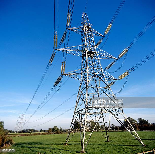 Electricity power transmission pylons in field