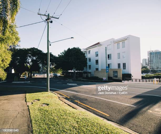 electricity pylon amidst road in city against clear sky - street stock pictures, royalty-free photos & images