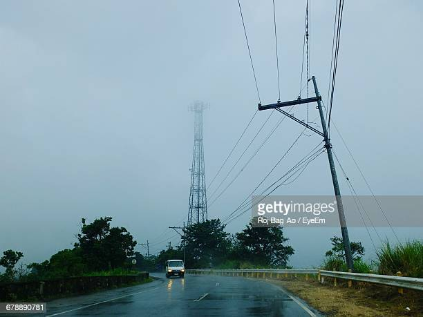 Electricity Pylon By Wet Road Against Sky During Rainy Season