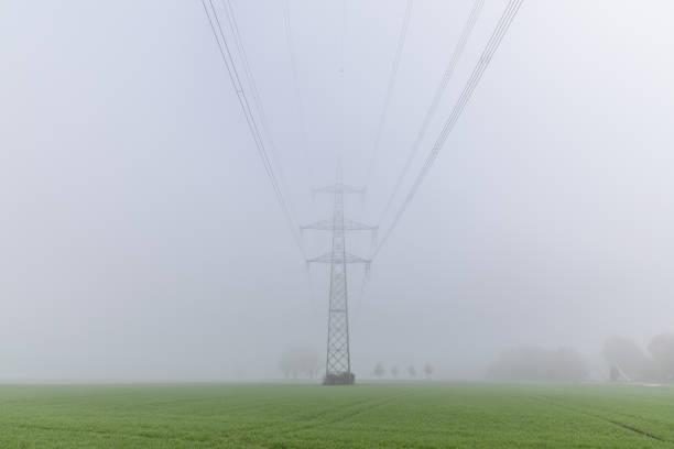 Electricity pylon in fog above green field