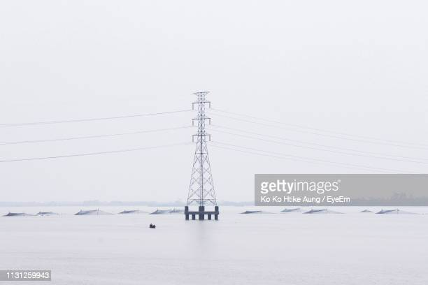 electricity pylon in sea against sky during winter - ko ko htike aung stock pictures, royalty-free photos & images