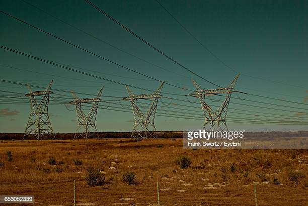 electricity pylon on field against blue sky - frank swertz stock-fotos und bilder