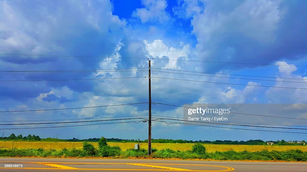 Electricity Pylon On Field Against Cloudy Sky : Stock Photo