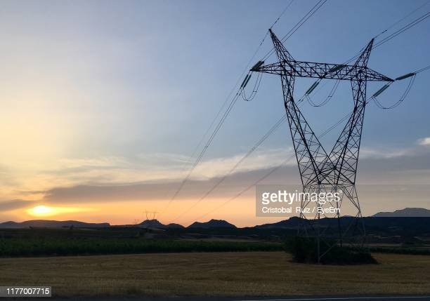 electricity pylon on land against sky during sunset - cristobal ruiz eyeem fotografías e imágenes de stock