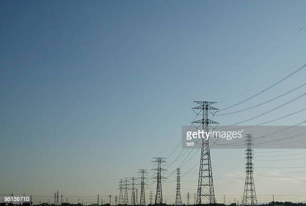 electricity pylons and power lines at dusk - コード ストックフォトと画像