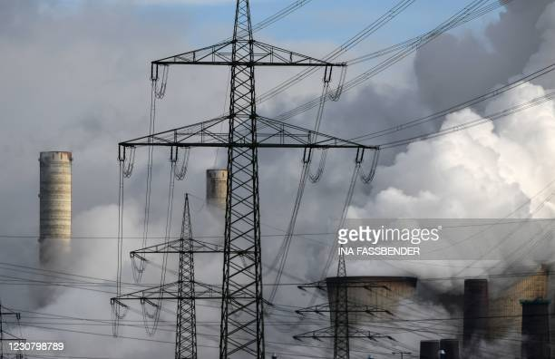 Electricity pylons are seen in front OF the cooling towers of the coal-fired power station of German energy giant RWE in Weisweiler, western Germany,...
