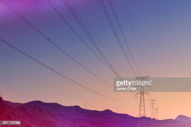 electricity pylons at sunset - energieindustrie stock-fotos und bilder