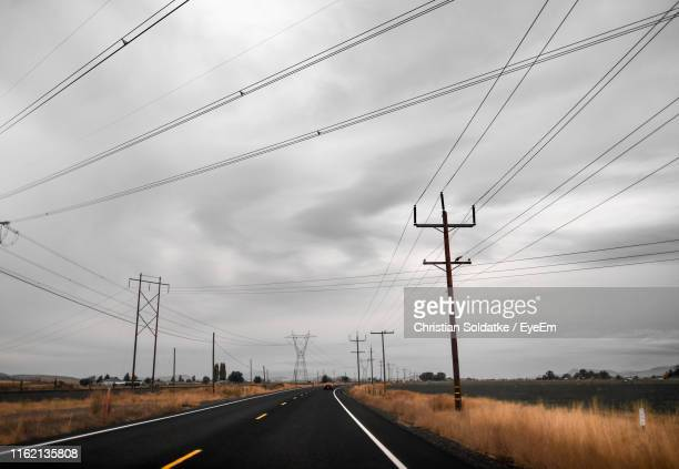 Electricity Pylons By Road Against Sky