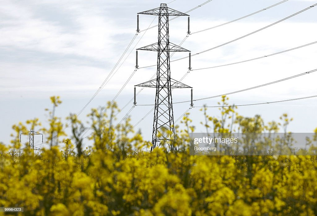 Electricity pylons carry high voltage power lines across a field of rapeseed in Hampshire, U.K., on Wednesday, May 19, 2010. Electricity use may have peaked today at 45,030 megawatts, reducing the cushion of spare capacity available to the network to 7,466 megawatts, according to data from National Grid Plc. Photographer: Rupert Hartley/Bloomberg via Getty Images