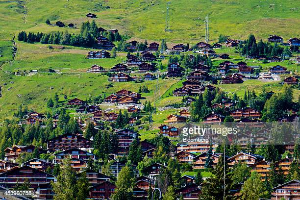 Electricity pylons carry power cables up a hillside as traditional Swiss chaletstyle houses and apartments blocks stand in Verbier Switzerland on...