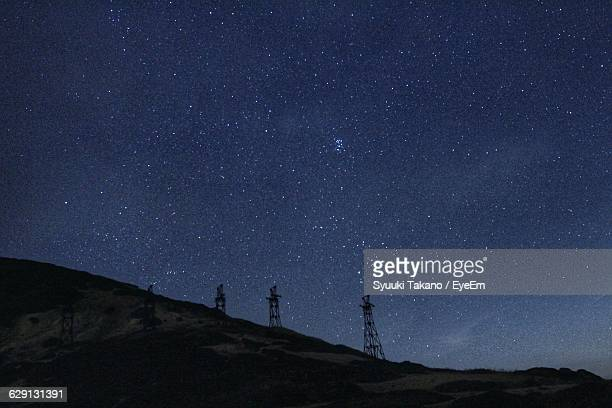 Electricity Pylons On Hill Against Starry Sky
