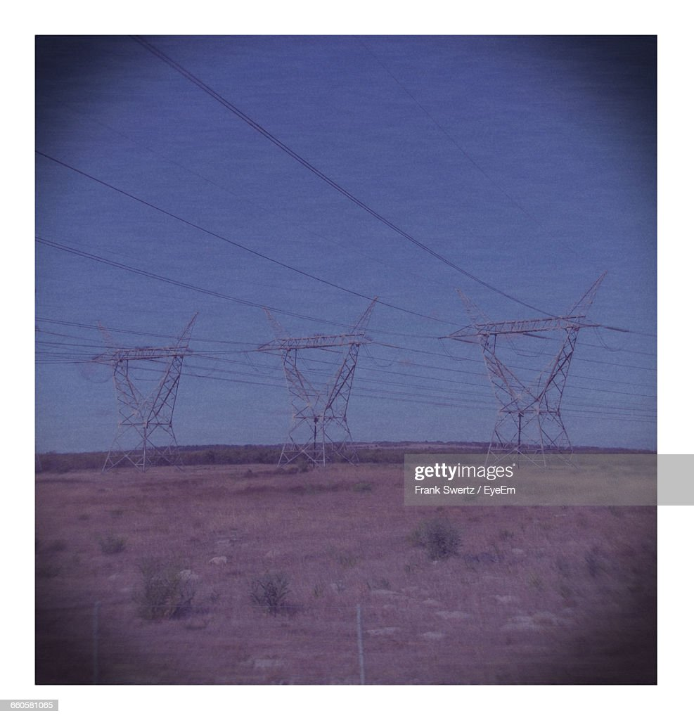 Electricity Pylons On Landscape Against Sky : Stock-Foto