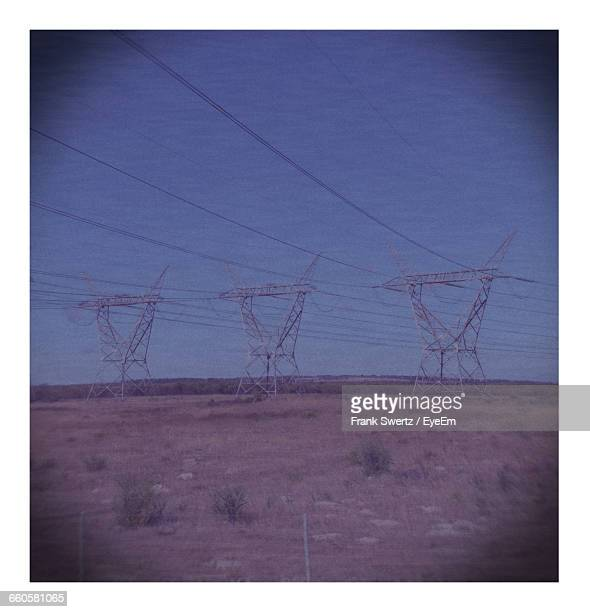 electricity pylons on landscape against sky - frank swertz stockfoto's en -beelden
