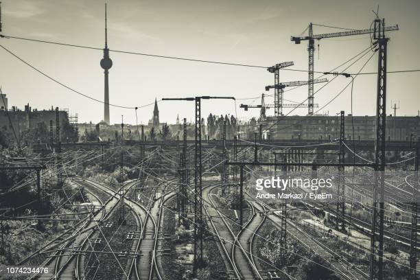 Electricity Pylons On Railroad Tracks In City Against Sky