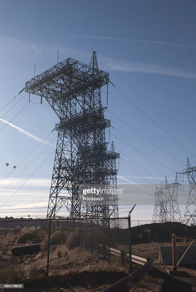 Electricity pylons over a dam : Stock Photo