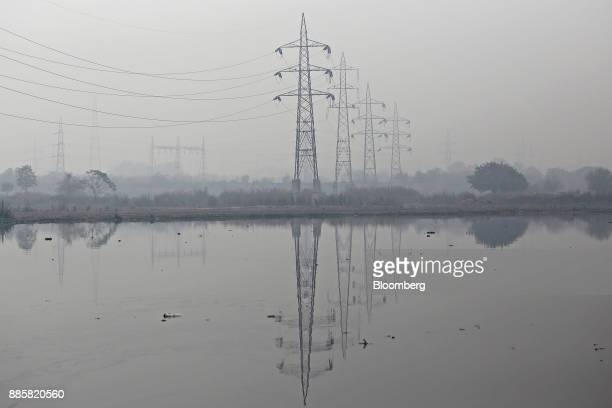Electricity pylons reflected in a river are shrouded in smog in New Delhi India on Monday Dec 4 2017 The World Health Organizationwarnsthat...