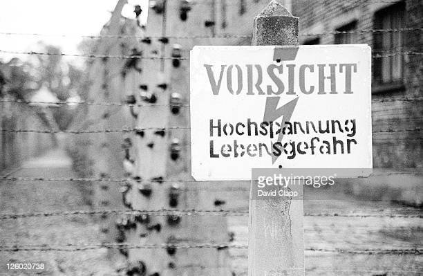 electrocution sign on electric fence: 'caution high voltage mortal danger'. birkenau concentration camp, auschwitz, poland - birkenau stock pictures, royalty-free photos & images