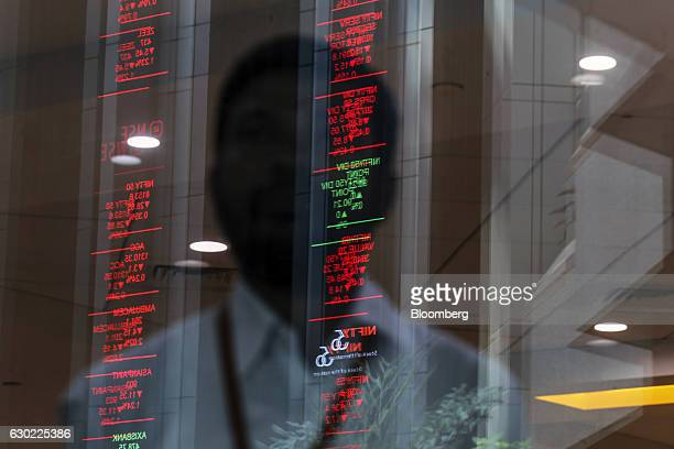 Electronic board indicating the latest stock figures are reflected in a glass facade at the National Stock Exchange of India Ltd in Mumbai India on...