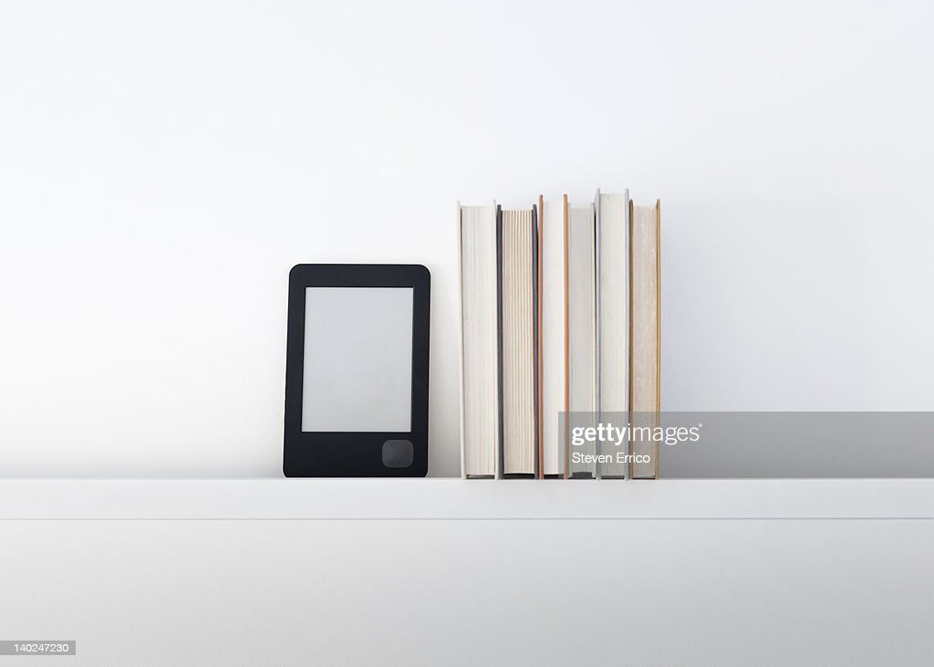 Electronic book reader next to traditional books : Stock Photo