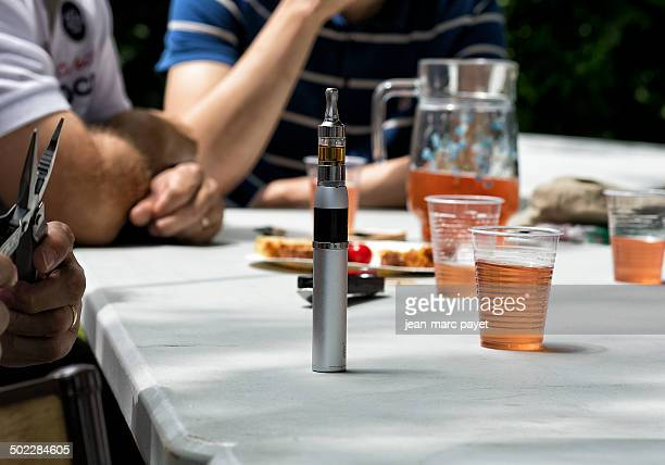Electronic cigarette on a table Electronic cigarette on a table during a moment of conviviality with friends who drink a aperitif outdoors
