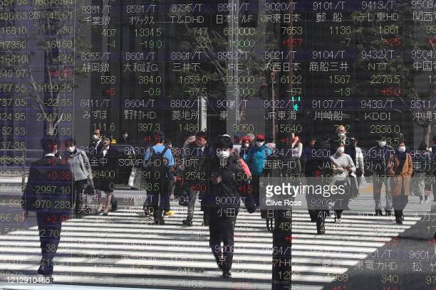 Electronic displays reflect the current stock market trends as the financial world continues to react to the COVID-19 pandemic in Tokyo on March 16,...