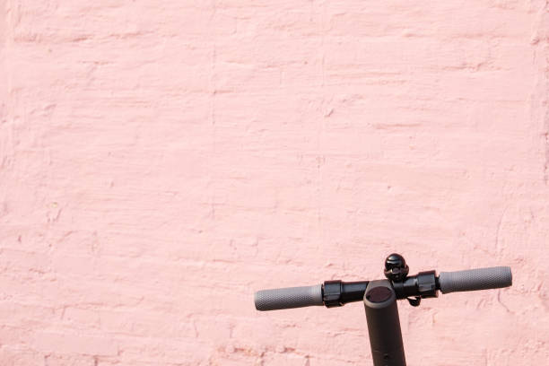 electronic scooter against pink brick wall