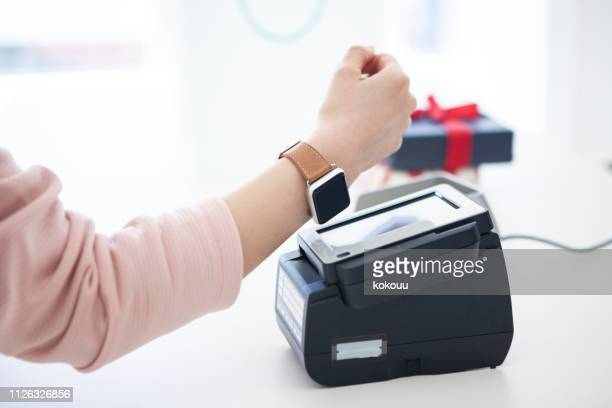 electronic settlement with smart watch - smart watch stock pictures, royalty-free photos & images