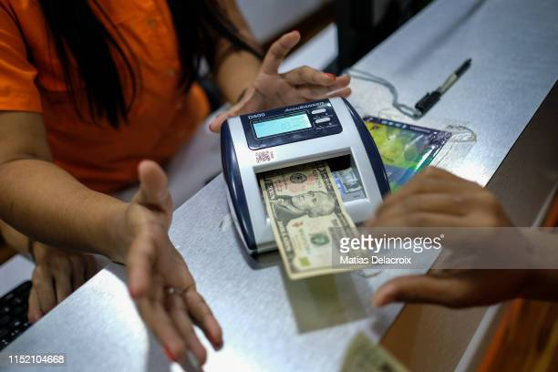 Electronic store clerks check a US dollar bill on June 26 2019 in Caracas Venezuela Everyday more Venezuelans use American dollar notes to buy...