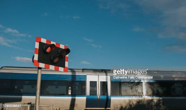 electronic train speeding past a level crossing - commuter stock pictures, royalty-free photos & images