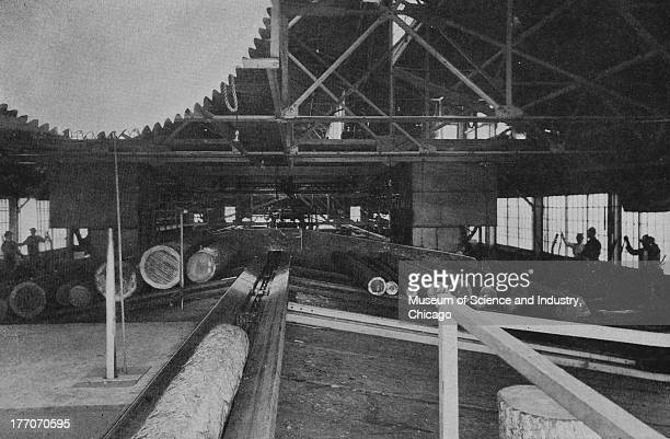 Electronically Driven Saw Mills Cut 11372 black and white photograph of the inside room of a sawmill showing a log haul and overhead circular cutoff...