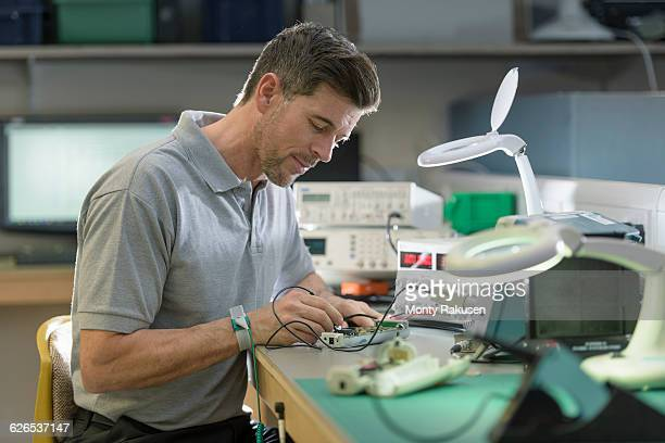 Electronics engineer assembling components in electronics factory