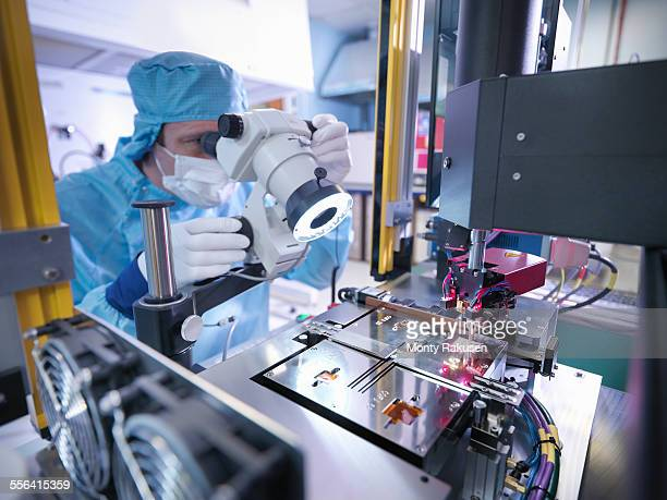 Electronics worker checking component in clean room