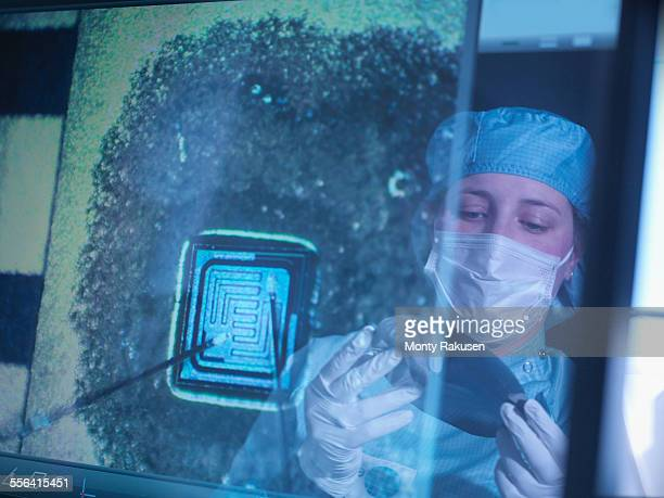 Electronics worker holding silicon wafer reflected in screen in clean room