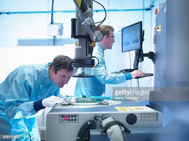Electronics workers checking components in clean room laboratory