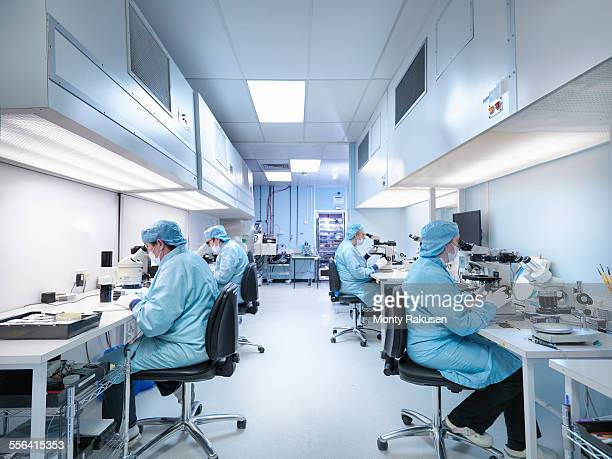 electronics workers in clean room assembling electronic components - 半導体 ストックフォトと画像